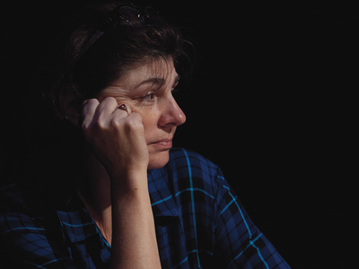 Actress Irina Dubova as Mama, with a hand on her face and wistful expression, profile, wearing blue flannel.